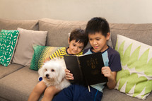 brothers sitting on a couch reading a Bible with their pet dog