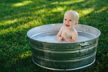 baby in a metal tub outdoors