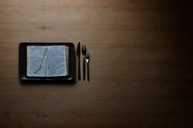 Table set with a plate, knife and two forks. On the plate, in stead of physical food there is spiritual food: The bible. The bible is an old translation into danish, revised to fit the norwegian language. It is printed in gothic script.   For increasing versatility this photo is offered with additional negative space.