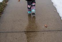boots on a wet sidewalk