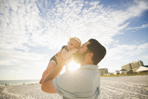 a father kissing his infant daughter on a beach