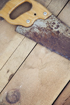 rusty saw on a wood floor