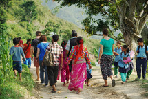 school children and villagers walking on a dirt path