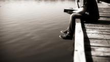 A young adult, white man, sitting at the edge of a dock reading his Bible