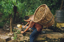 a boy gathering crops with a basket on his back