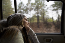 woman looking out a car window