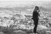 woman with a camera on a mountain top