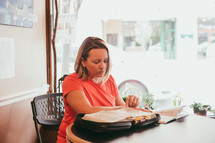 a woman sitting at a table reading a Bible