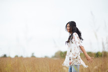 a young woman walking through a field with open arms