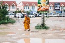 a monk in a orange robe cross a parking lot