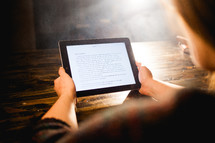 a woman reading a Bible on an iPad