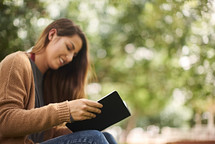 a woman sitting on a park bench reading a Bible