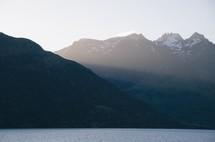 snow on mountain peaks near a lake