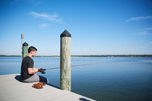 a man sitting and fishing on a pier