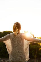 a woman standing outdoors at sunset with outstretched arms