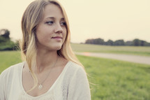 Teenage girl standing outdoors and looking back over her shoulder.