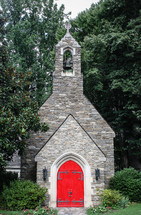 red doors to a stone church