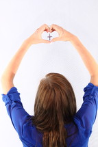 young woman holding up a cross and making a heart with her hands