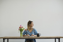 a woman sitting at a desk with a mug of coffee and a vase of tulips reading a Bible