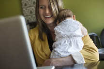 working mom, mother typing on a computer while holding her infant