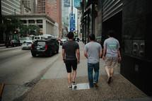 men walking down a downtown city sidewalk