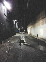 puddle of water in an alley at night