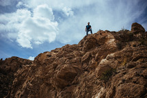 A man standing on top of a cliff.