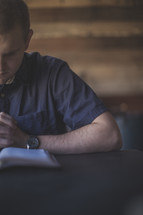 A man with hands folded in prayer over an open Bible