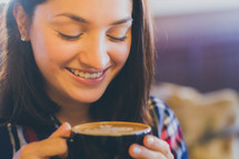 A young woman smiling with a cup of coffee
