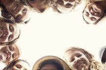 a group of happy teenage girl's heads looking down at the camera
