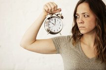 grumpy woman holding an alarm clock