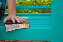 a hand on a Bible on a bench