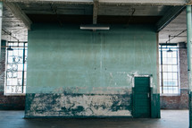A large empty room with old walls and a green door.
