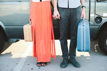 a couple standing in front of a van holding suitcases