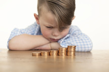 a little boy looking at his stack of coins.