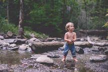 toddler boy playing in a stream