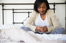 young woman sitting in bed texting