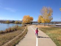 a toddler girl riding a bike along a trail