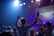 a man standing with raised hands and worship leaders leading a congregation in song