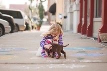girl child playing with a puppy