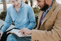 two men sitting on a bench reading a Bible and discussing scripture