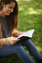 a woman reading a Bible sitting in the grass