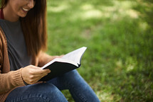 a woman sitting in grass reading a Bible