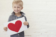 toddler boy happily holding a painting of a heart