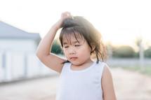 child scratching her head