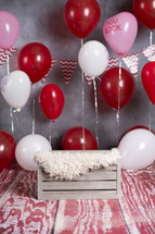 crate and red balloons