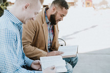two men sitting on a park bench reading Bibles and discussing scripture