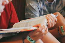 teen boy reading a Bible at a Bible study