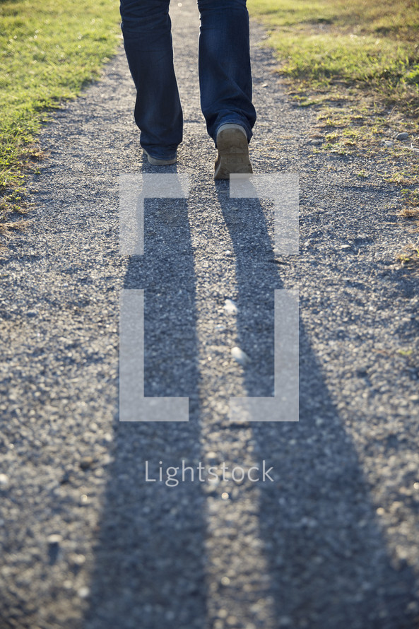 man walking on a gravel road