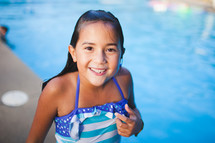 a girl child in a bathing suit by a swimming pool